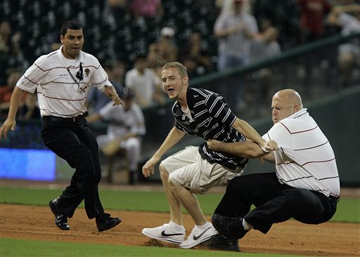 A security guard tackles a fan who ran out onto the field in the final inning of the Milwaukee Brewers 9-1 win over the Houston Astros in a baseball game Tuesday, Sept. 18, 2007 in Houston. Three fans ran out onto the field and were promptly arrested. (AP Photo/Pat Sullivan)